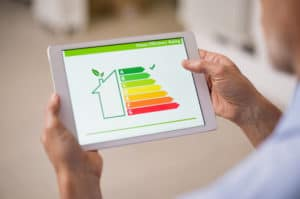Hand holding digital tablet and looking at house efficiency rating. Detail of house efficiency rating on digital tablet screen. Concept of ecological and bio energetic house. Energy class.