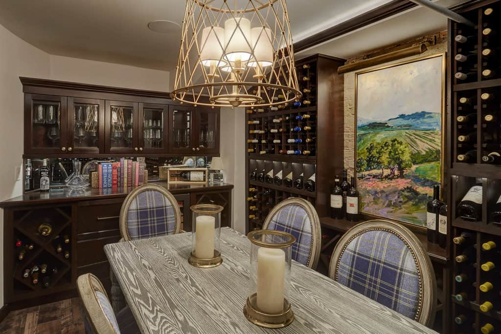 A custom wine cellar with gold trimmed blue chairs, a table with gold trimmed candles, and overhead lighting.