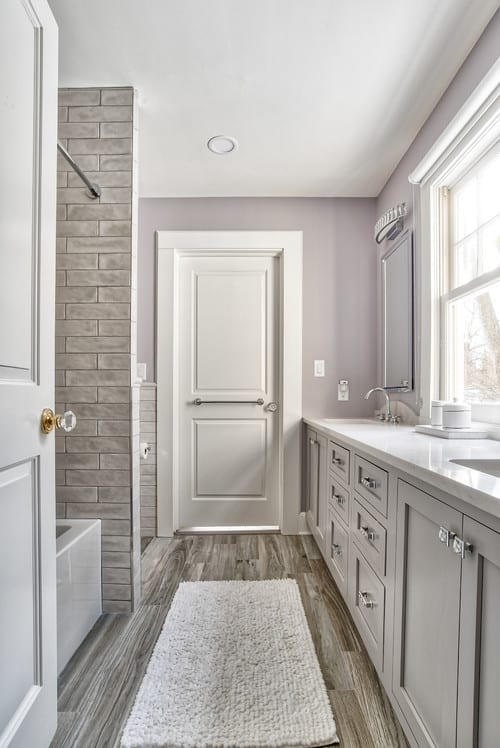 A gray and white Jack and Jill Bathroom with wooden floors and a stone tiled bath