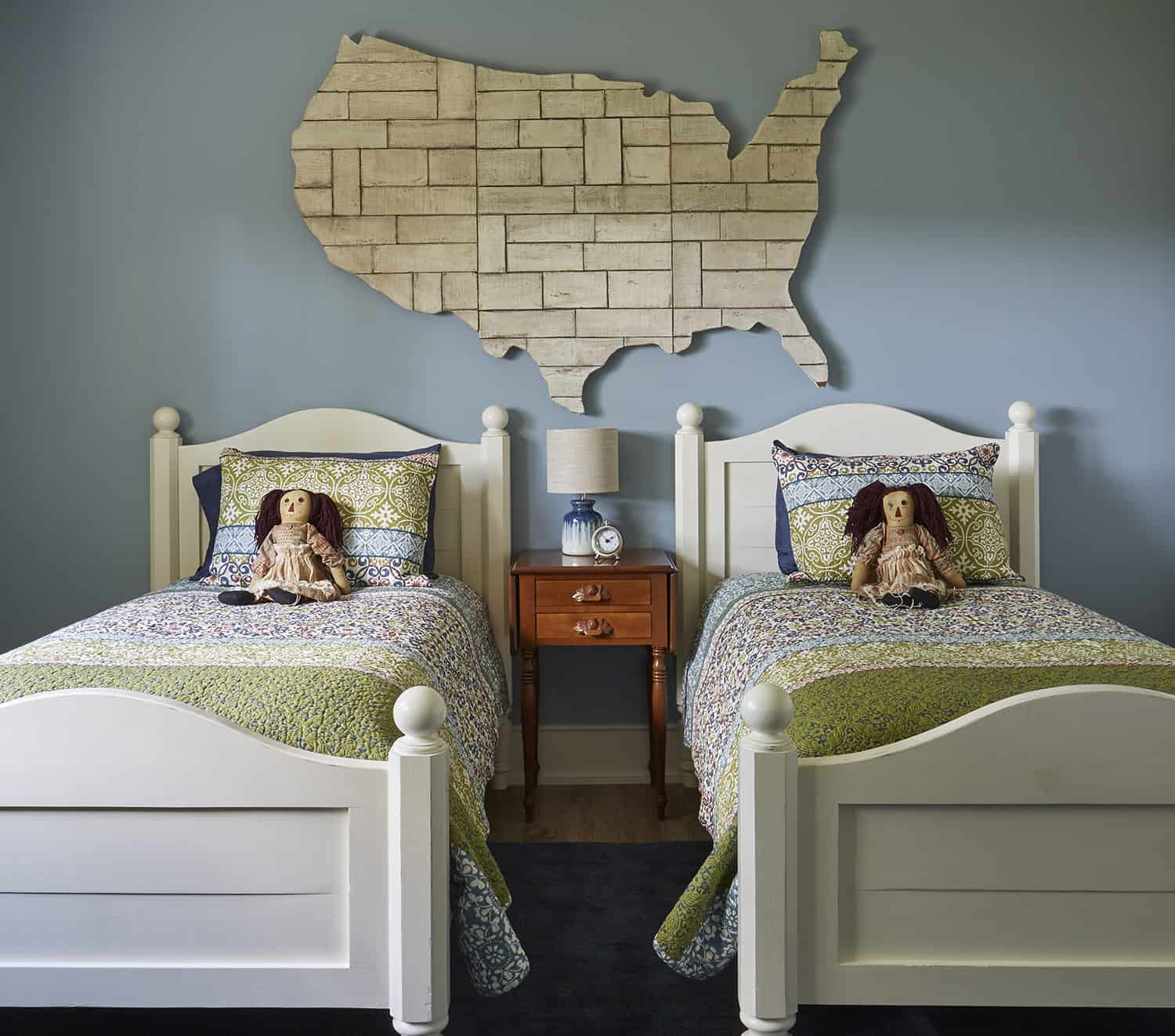 twin beds with dolls on bed and large wooden us map